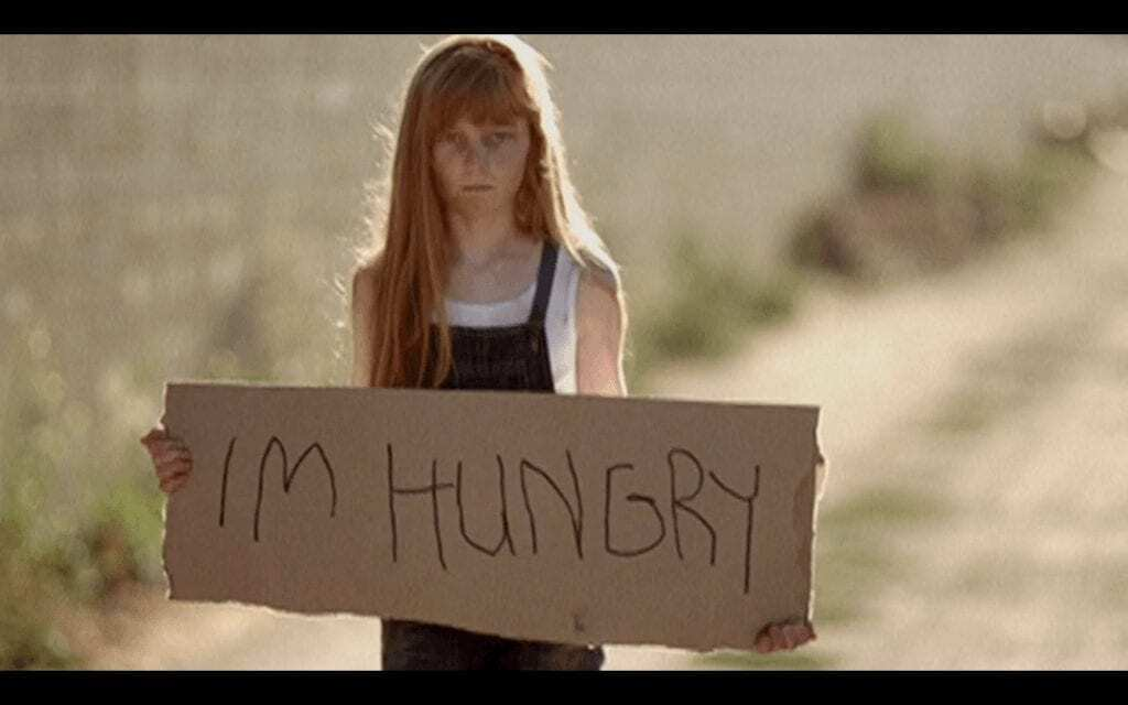 hungry kid holding up a sign that reads 'i'm hungry'
