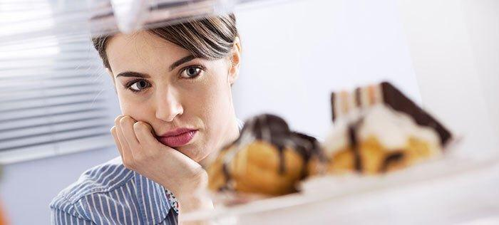 woman staring at piece of cake and experiencing intense cravings wanting to reach for food but holding herself back